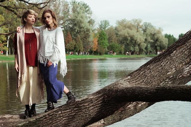 Zdjęcie dwóch pięknych kobiet pozujących na drzewie w pobliżu jeziora.