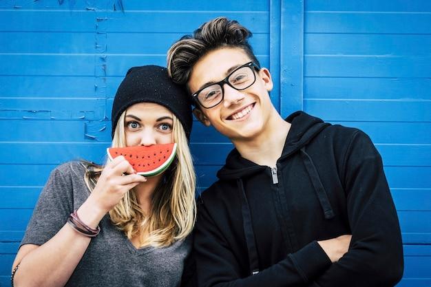 Zdjęcie dwóch przyjaciół stojących obok siebie płacących razem - ona bawi się arbuzem - on jest w okularach