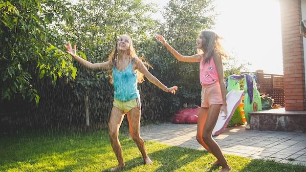 Zdjęcie dwóch szczęśliwych sióstr roześmianych w mokrych ubraniach tańczących pod kroplami wody z węża ogrodowego w ogrodzie. rodzinna zabawa i zabawa na świeżym powietrzu latem