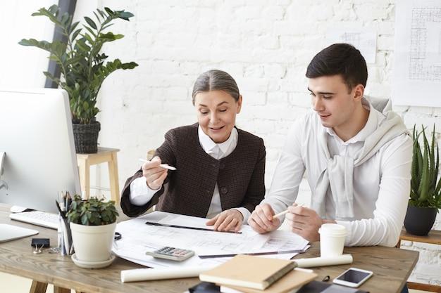 Zdjęcie dwóch wesołych, profesjonalnych projektantów, dojrzałej kobiety i młodego mężczyzny pracujących razem nad projektem budynku mieszkalnego, siedzących przy biurku, omawiających pomysły na tworzenie przestrzeni funkcjonalnej i dekorację