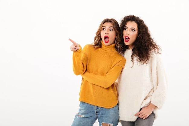 Zdjęcie dwóch zszokowanych dziewcząt w swetrach wskazujących i odwracających wzrok nad białym bachground