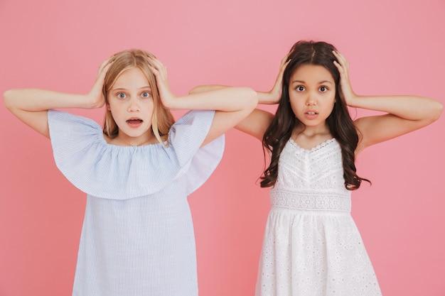 Zdjęcie dwóch zszokowanych lub przestraszonych dziewcząt w wieku 8-10 lat ubranych w sukienki zakrywające uszy lub chwytające głowy z otwartymi ustami, odizolowane na różowym tle