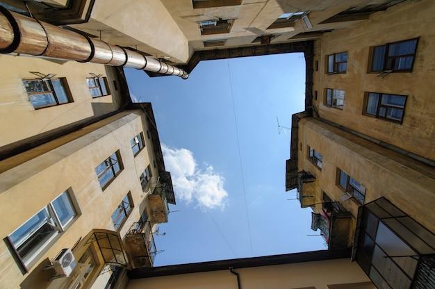 Zdjęcie dziedzińca, na którym domy mają kształt kwadratu. zobacz w kierunku nieba. biedna stara dzielnica miasta.
