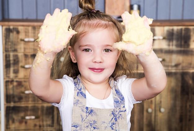 Zdjęcie dziewczynki pokazuje brudne ręce w cieście