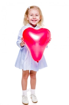 Zdjęcie dziewczynki w niebieskiej sukience trzyma czerwony balon w kształcie serca