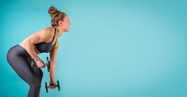 Zdjęcie dziewczyny fitness ćwiczącej z hantlami na niebieskim tle wolne miejsce na kopię