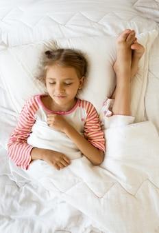 Zdjęcie dziewczyny leżącej obok stóp siostry na poduszce
