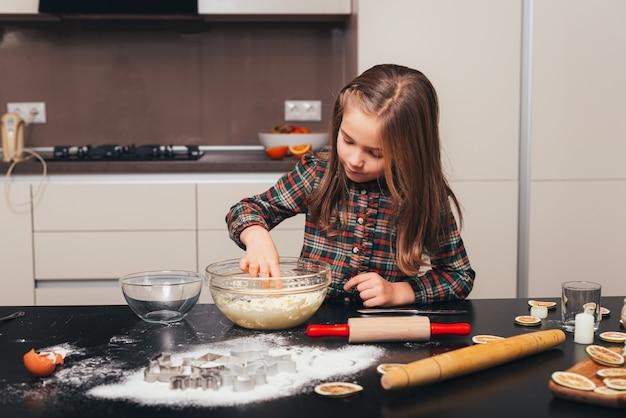Zdjęcie dziewczyny przygotowującej herbatniki w kuchni