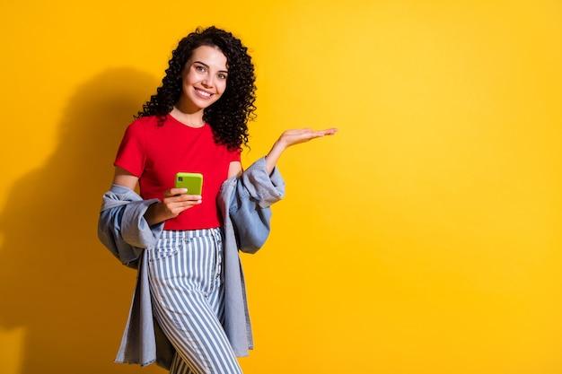 Zdjęcie dziewczyny trzyma telefon bezpośredni palec wskazujący wygląd pustej przestrzeni nosić paski dżinsy czerwona koszulka kurtka na białym tle żółty kolor tła