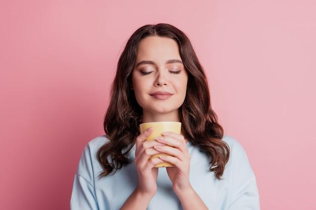 Zdjęcie dziewczyny trzymaj filiżankę pij kawę ciesz się aromatem zamkniętymi oczami