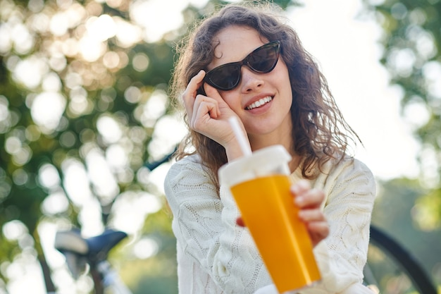 Zdjęcie dziewczyny w okularach przeciwsłonecznych z butelką wody w ręku