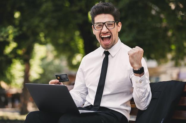 Zdjęcie ekstatycznego biznesmena w garniturze krzyczy siedząc na ławce w zielonym parku i pracując na laptopie w słoneczny dzień