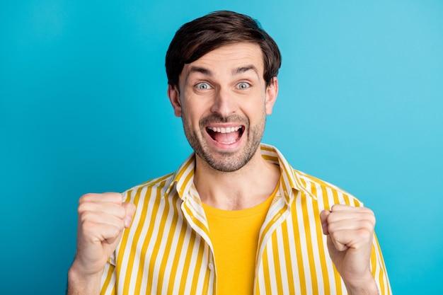 Zdjęcie ekstatycznego mężczyzny podnosi pięści krzyczeć tak wygrana drużyna piłkarska marzenie narodowe pragnienie mecz nosić dobrze wyglądające ubrania izolowane na niebieskim tle