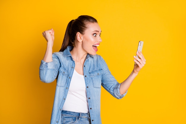 Zdjęcie ekstatycznej szalonej dziewczyny użyj smartfona czytaj serwis społecznościowy subskrybenci subskrybenci wiadomości podnieś pięści krzycz tak nosić styl stylowy modny strój na białym tle jasny połysk kolor tła