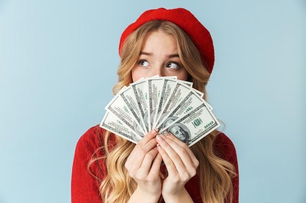 Zdjęcie eleganckiej blond kobieta 20s na sobie czerwony beret, trzymając kilka banknotów pieniędzy na białym tle