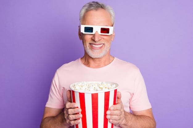 Zdjęcie emerytowanego starca trzymać papierowe pudełko popcorn wygląd aparat nosić 3d specyfikacje różowy t-shirt na białym tle fioletowy kolor tła
