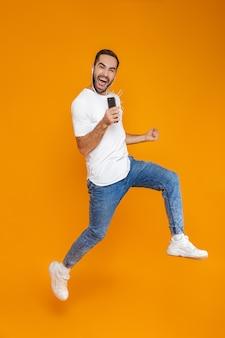 Zdjęcie emocjonalnego człowieka 30s śpiewającego podczas korzystania ze słuchawek i telefonu komórkowego, na białym tle