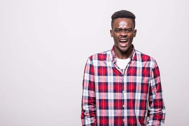 Zdjęcie emocjonalnego krzyczącego młodego człowieka afrykańskiego stojącego na białym tle.