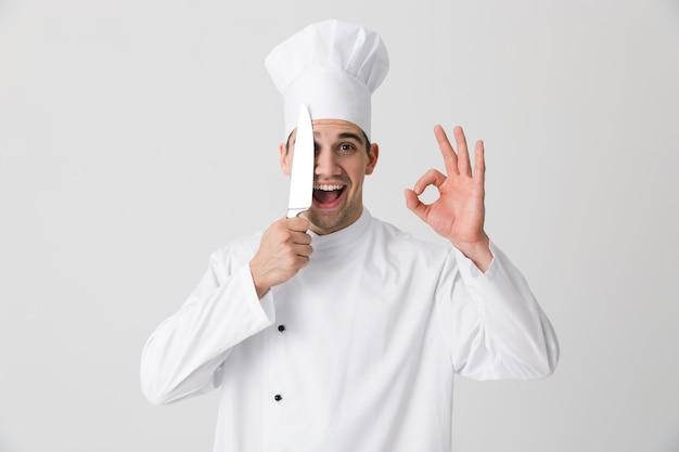 Zdjęcie emocjonalnego młodego człowieka szefa kuchni w pomieszczeniu na białym tle na tle białej ściany, trzymając nóż pokazujący w porządku gest.