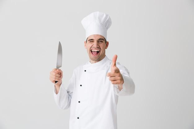 Zdjęcie emocjonalnego młodego człowieka szefa kuchni w pomieszczeniu na białym tle na tle białej ściany trzymając nóż wskazujący.