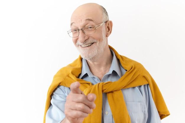 Zdjęcie emocjonalnego, przystojnego starszego mężczyzny z łysą głową i szarym zarostem, uśmiechniętego szeroko i wskazującego palcem na aparat, śmiejącego się z zabawnej historii lub żartu, pozującego na białym tle na białej ścianie studia