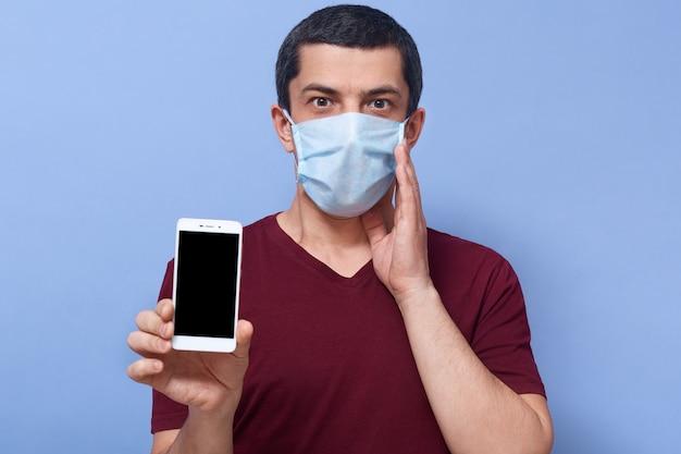Zdjęcie emocjonalnie zszokowanego faceta, który przykłada dłoń do twarzy, trzyma smartfon, wpada w panikę, używa urządzenia, zostaje w domu, boi się koronawirusa. koncepcja ludzi i pandemii.
