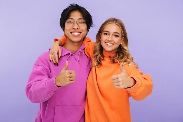 Zdjęcie emocjonalnych młodych studentów przyjaciół para stojących na białym tle, pokazując kciuki do góry.