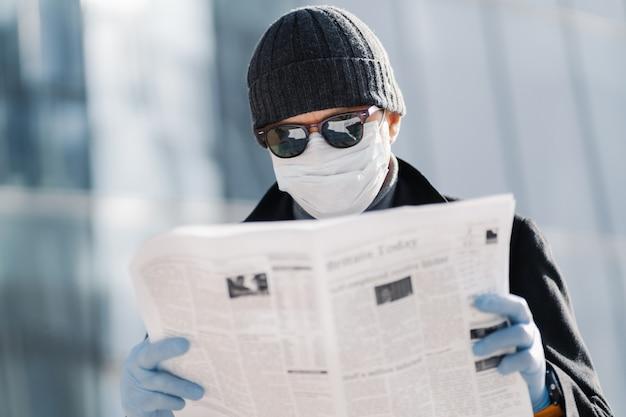 Zdjęcie europejczyka nosi ochronną maskę medyczną i rękawiczki, spaceruje po mieście na zewnątrz, czyta artykuł o wybuchu wirusa w różnych krajach, stosuje środki ochronne podczas rozprzestrzeniania się koronawirusa