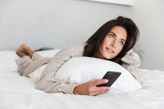 Zdjęcie europejki 30-letniej korzystającej z telefonu komórkowego, leżącej w łóżku z białą pościelą w jasnym pokoju