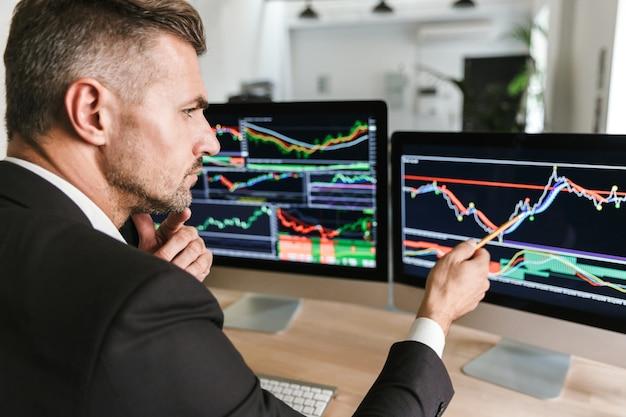 Zdjęcie europejskiego biznesmen 30s na sobie garnitur siedzi przy stole w biurze i pracuje z grafiką i wykresami na komputerze