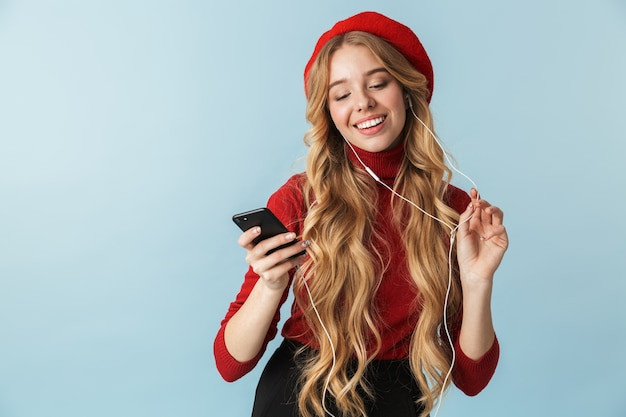 Zdjęcie europejskiej dziewczyny 20s noszących słuchawki do słuchania muzyki na telefon komórkowy na białym tle