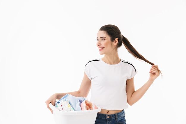 Zdjęcie europejskiej kobiety gospodyni domowej w wieku 20 lat ubranej w odzież codzienną niosącą kosz na pranie z brudnymi, czystymi ubraniami na białym tle nad białą ścianą