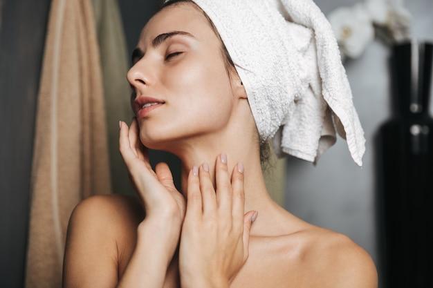 Zdjęcie europejskiej kobiety z ręcznikiem na głowie masuje twarz po kąpieli