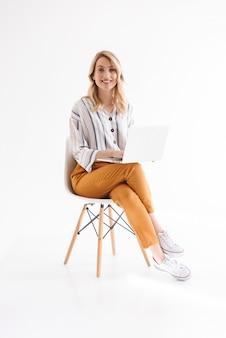 Zdjęcie europejskiej ładnej kobiety na sobie ubranie, uśmiechając się i za pomocą laptopa siedząc w fotelu na białym tle nad białą ścianą