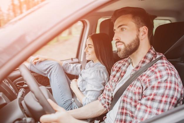 Zdjęcie faceta jadącego samochodem na drodze. on patrzy prosto na koncentrację. młody człowiek wygląda poważnie. dziewczyna siedzi obok niego. ułożyła nogi w szybie samochodu i uśmiechnęła się.