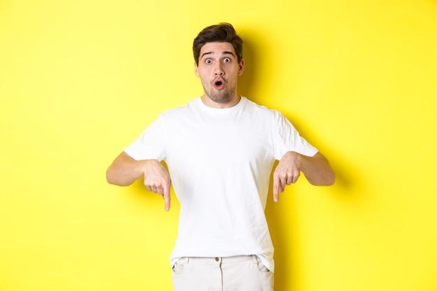 Zdjęcie faceta pod wrażeniem wskazującego palcami w dół, dyszącego zdumiony i patrzącego w kamerę, stojącego na żółtym tle.