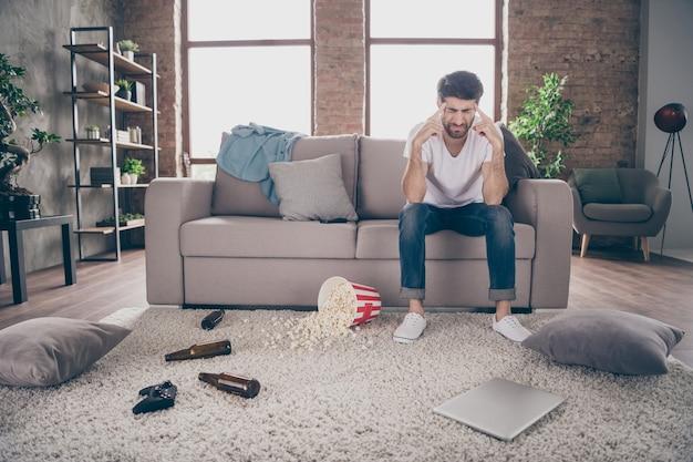 Zdjęcie faceta rasy mieszanej siedzącej na kanapie trzymającej skronie odurzone butelki po piwie popcorn na podłodze miał szalony wieczór kawalerski cierpi na kaca rano ból głowy niechlujny mieszkanie w domu
