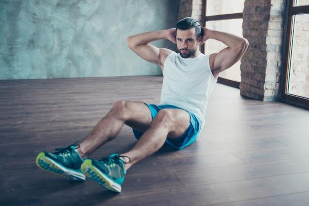 Zdjęcie faceta sportowca macho robi statyczne przysiady siedząc na podłodze zdeterminowana osoba odzież sportowa podkoszulek spodenki tenisówki dom treningowy okna w pomieszczeniu