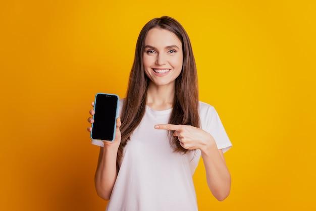 Zdjęcie fajnej damy z ekranem dotykowym telefonu z palcem w pustej przestrzeni nosić białą koszulkę pozującą na żółtym tle