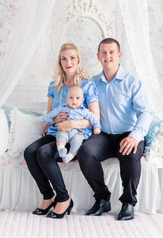 Zdjęcie family time. tata i mama siedzą na kanapie z synkiem