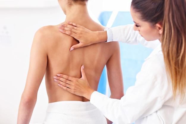 Zdjęcie fizjoterapeutki pomagającej pacjentowi z problemami z kręgosłupem w klinice