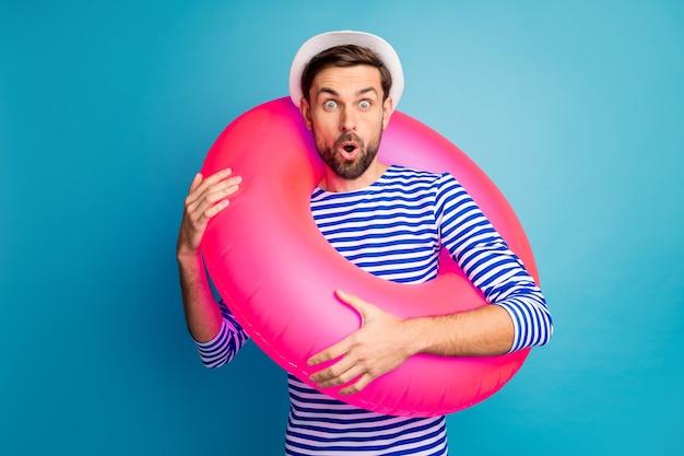 Zdjęcie funky podekscytowany przystojny facet turystyczny trzymaj kolorowe różowe gumowe koło ratunkowe niskie letnie ceny odzież na zakupy w paski marynarska koszula czapka na białym tle niebieski kolor