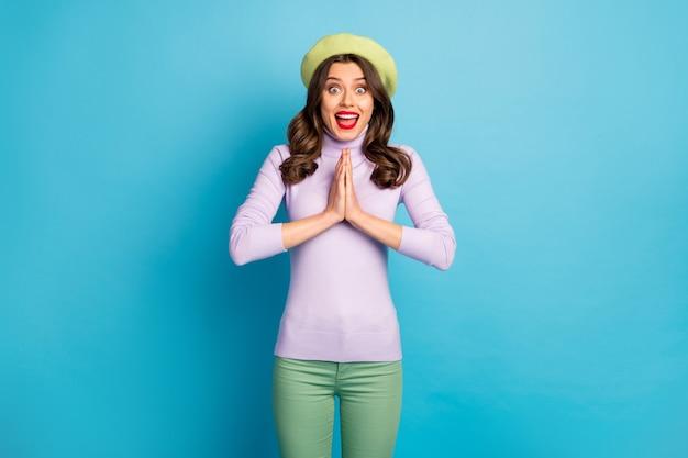 Zdjęcie funky podróżniczki podekscytowane uczucia trzymaj ręce razem błagając chłopaka o odwiedzenie jeszcze jednego sklepu nosić zielony beret fioletowy sweter spodnie na białym tle niebieski kolor ściana
