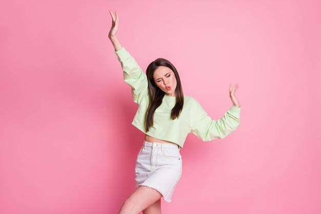 Zdjęcie funky śmiesznej dziewczyny młodzieżowej podniesie ręce cieszyć się muzyką tańczyć nosić dobrze wyglądające ubrania pulower na białym tle nad pastelowym kolorem tła
