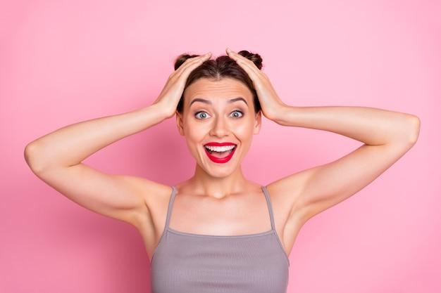 Zdjęcie funky youngster girl ładne bułeczki czerwona szminka otwarte usta ramiona na głowie dobra wiadomość uszczęśliwiona nosić swobodny letni szary podkoszulek izolowany pastelowy różowy kolor