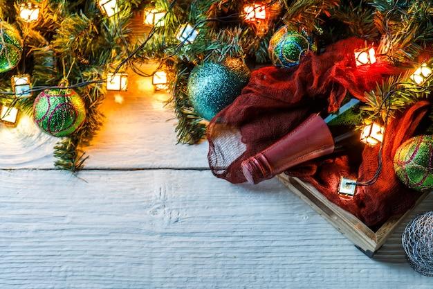 Zdjęcie gałęzi jodłowych, bombek, butelki wina szmatką na białym stole.