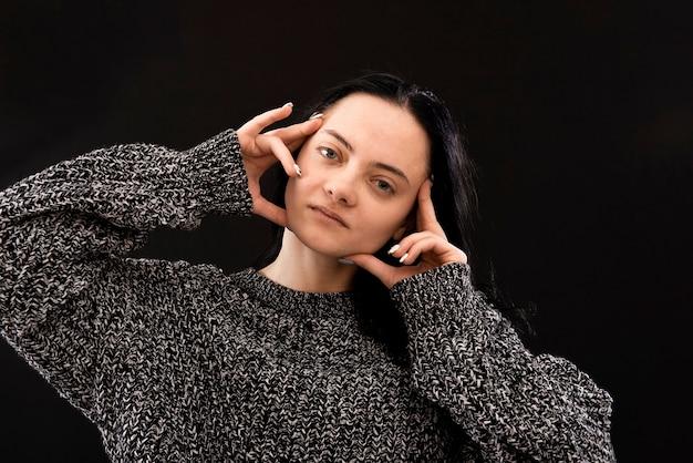 Zdjęcie głowy młodej kobiety z silnym bólem głowy, gorączką lub migreną trzymającą ręce na skroniach w pobliżu twarzy