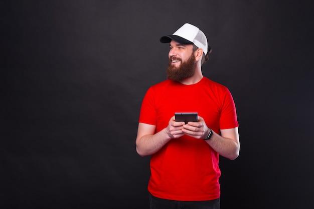 Zdjęcie hipster brodaty mężczyzna w czerwonej koszulce trzymając tablet i patrząc od hotelu na czarnym tle
