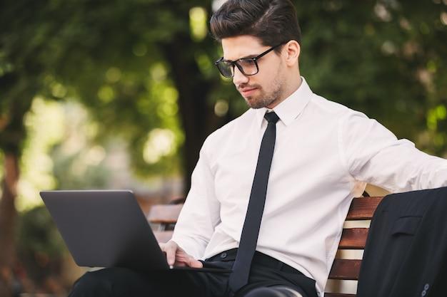 Zdjęcie inteligentnego biznesmena w garniturze siedzi na ławce w zielonym parku i pracuje na laptopie w słoneczny dzień