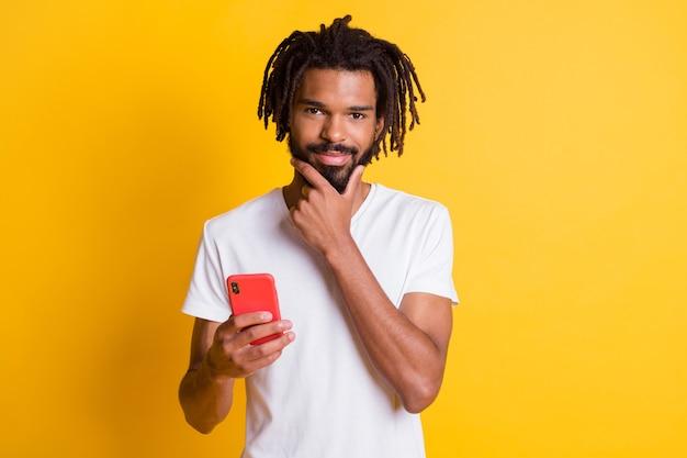 Zdjęcie inteligentnego studenta ciemnoskórego faceta trzyma telefon sprytne oczy ramię na brodzie nosi koszulkę na białym tle żółty kolor tła